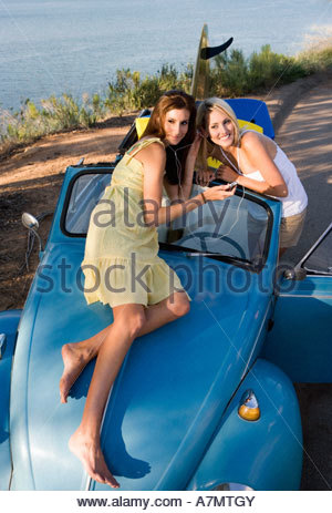 Teenage girls 17 19 listening to MP3 player on car bonnet sharing headphones elevated view - Stock Photo