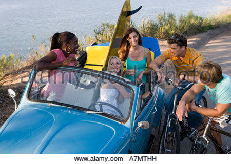 Teenagers (17-19) talking by roadside, girls in blue convertible car, boys on bicycles, elevated view - Stock Photo