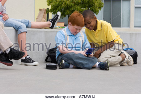 Children 9 11 sitting on wall outside school two boys sitting on ground playing video game - Stock Photo