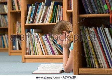 Girl 10 12 lying on floor beside bookshelf in library reading book profile - Stock Photo