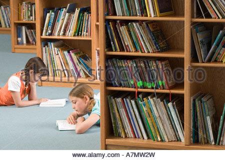 Two girls 10 12 lying on floor beside bookshelf in library reading books side view - Stock Photo