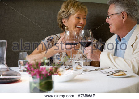 Senior couple dining in restaurant drinking red wine making celebratory toast smiling - Stock Photo