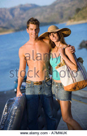 Teenage couple 17 19 standing near lake boy holding inflatable girl wearing sun hat portrait - Stock Photo