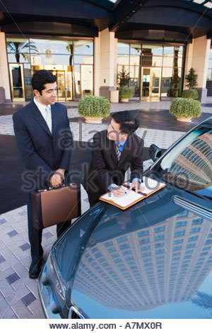 Two businessmen standing beside car outside hotel man signing contract smiling - Stock Photo