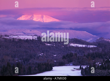 Sunrise on a snow covered landscape with Mt Hood peeking through clouds, as viewed from Jonsrud viewpoint near Sandy, - Stock Photo