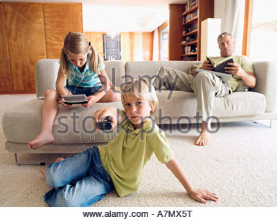 Father reading book on sofa at home boy 6 8 changing tv channel girl 6 8 playing video game - Stock Photo