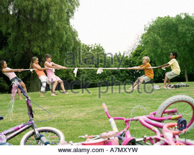 Group of children 7 9 playing tug of war on grass in park profile bicycles in foreground - Stock Photo