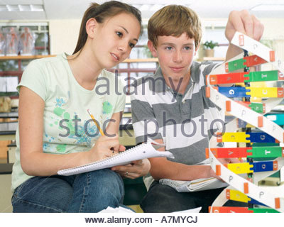 Teenage boy and girl 15 17 sitting at desk in classroom studying DNA model - Stock Photo