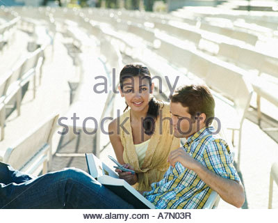 Young couple sitting in outdoor theatre woman holding mobile phone smiling man reading book - Stock Photo