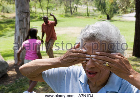 Children 6 10 playing hide and seek with grandparents in park senior woman covering eyes - Stock Photo