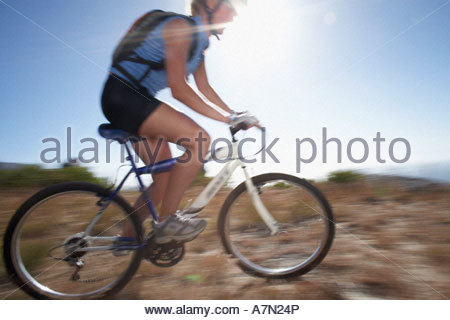 Mountain biker cycling across extreme terrain in bright sunlight side view lens flare - Stock Photo