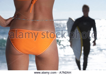 Young woman in orange bikini watching surfer leaving sea rear view mid section close up - Stock Photo