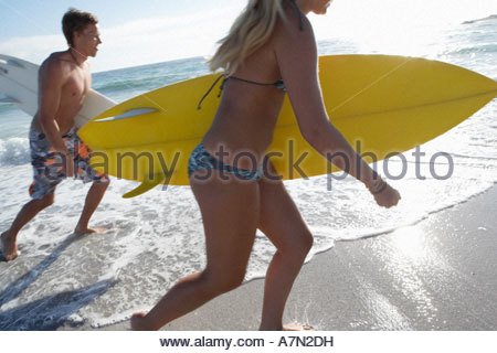 Young couple walking in surf at beach carrying surfboards side view - Stock Photo