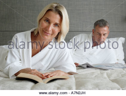 Couple in bathrobes relaxing on hotel bed man reading newspaper focus on woman with book - Stock Photo