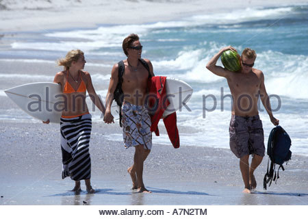 Three friends walking on beach couple with surfboards holding hands man carrying watermelon - Stock Photo