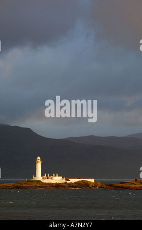 Lighthouse on Eilean Musdile in the Sound of Mull Western Isles Scotland in early morning sunlight with dark stormy - Stock Photo
