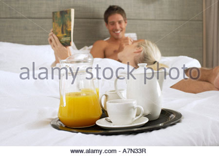Couple in bathrobes relaxing on hotel bed focus on orange juice and coffee on tray in foreground - Stock Photo