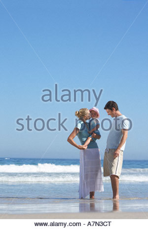 Two generation family standing on beach at water s edge mother holding daughter 2 4 - Stock Photo
