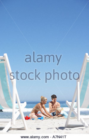 Two generation family building sandcastles on sandy beach deckchairs in foreground - Stock Photo
