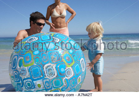 Two generation family playing with large turquoise beach ball sea in background - Stock Photo