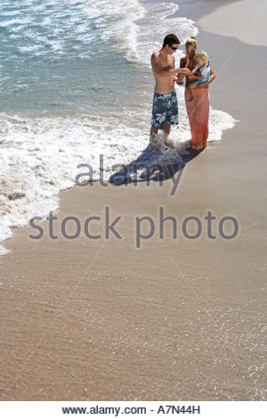 Family standing on beach in surf woman carrying daughter 2 4 elevated view - Stock Photo