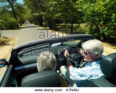 Senior couple driving in convertible car along country road rear view elevated view - Stock Photo