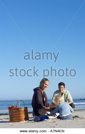 Two generation family sitting on sandy beach smiling rear view sea in background - Stock Photo