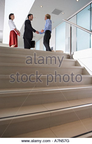 Two businessmen shaking hands at top of steps in lobby woman looking on side view low angle view - Stock Photo