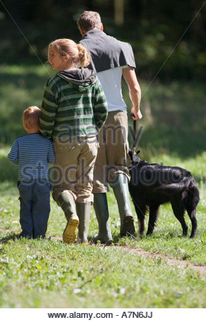 Two generation family walking dog in countryside wearing wellington boots rear view - Stock Photo