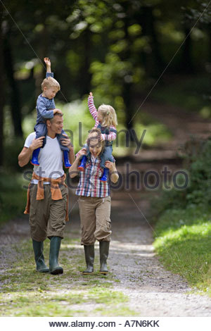 Two generation family walking along country path children 2 4 on parents shoulders front view - Stock Photo