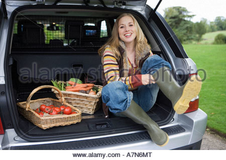 Woman sitting beside baskets of fresh vegetables in car boot putting on wellington boots smiling - Stock Photo