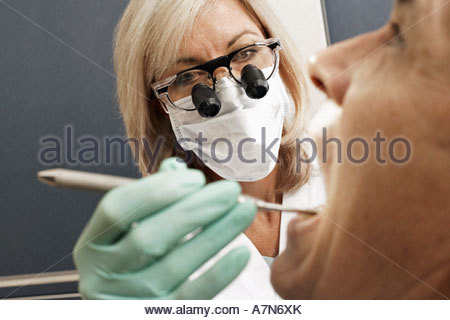 Female dentist wearing surgical loupes and mask examining patient using dental tool close up - Stock Photo