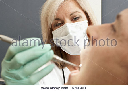 Female dentist wearing surgical mask examining patient using angled mirror close up - Stock Photo