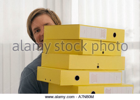 Businessman carrying stack of yellow folders in office face obscured smiling portrait - Stock Photo