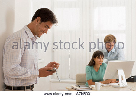 Business colleagues working at desk in office focus on man using electronic organiser in foreground - Stock Photo