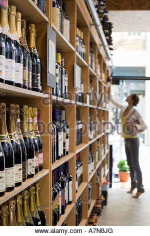 Female customer shopping in off licence looking at bottles of wine on shelf tip toeing profile - Stock Photo