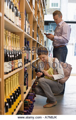 Customers shopping in off licence looking at bottles of wine on shelf woman crouching side view - Stock Photo