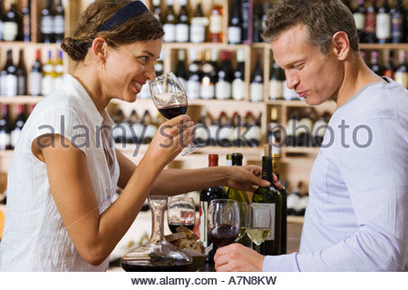 Couple wine tasting in off licence woman smelling glass of red wine man drinking profile smiling - Stock Photo