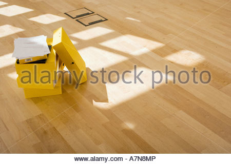 Documents on stack of yellow folders on office floor sunlight shining through window - Stock Photo