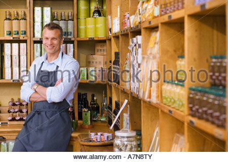 Male grocery shop owner in apron standing beside shelf display arms folded smiling portrait - Stock Photo