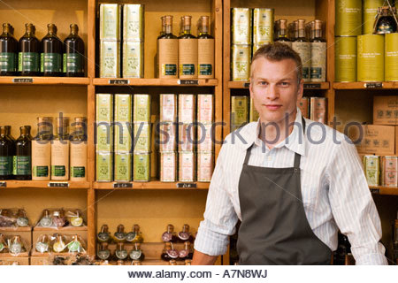 Male grocery shop owner in apron standing beside olive oil shelf display smiling portrait - Stock Photo