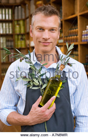 Male grocery shop owner in apron holding olive branch and bottle of oil smiling portrait - Stock Photo
