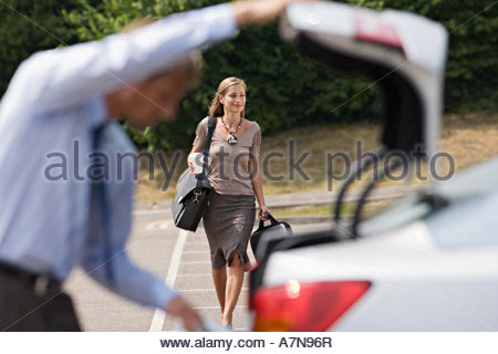 Man opening car boot in car park focus on businesswoman walking with luggage in background smiling - Stock Photo