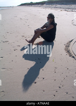 A woman sits in the sand on a beach - Stock Photo