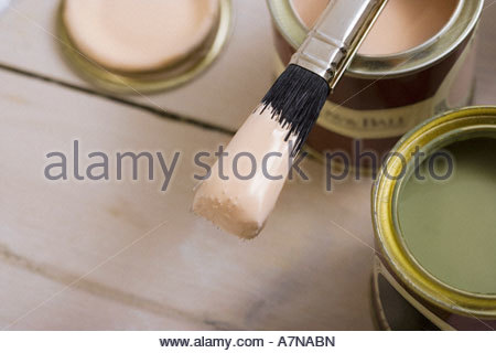 Small tins of paint and paintbrush on floor close up differential focus still life - Stock Photo