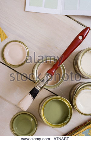 Small tins of paint and paintbrush on floor close up overhead view still life - Stock Photo