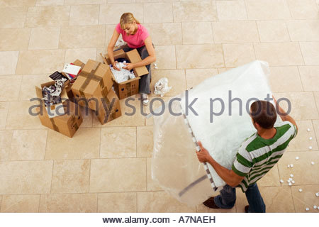 Couple moving house woman packing crockery in boxes man carrying table overhead view - Stock Photo
