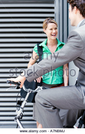 Businessman cycling on folding commuter bicycle flirting with businesswoman standing on pavement - Stock Photo