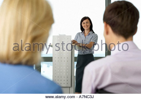 Businesswoman standing behind lectern giving presentation to colleagues focus on background - Stock Photo