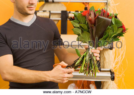 Male florist preparing bouquet of flowers in flower shop cutting stems with scissors mid section - Stock Photo